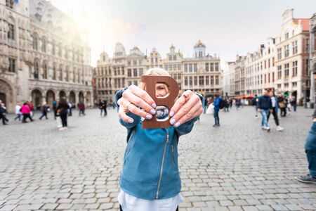 Young and happy woman with milk chocolate bar standing outdoors on the Grand place in Brussels in Belgium. Foto de archivo - 139861270