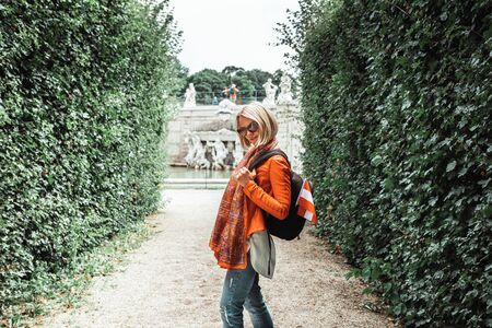 Young woman with a backpack and the flag of Austria stands in a classic park on a background of green trimmed topiart Belvedere Gardens in Vienna, Austria