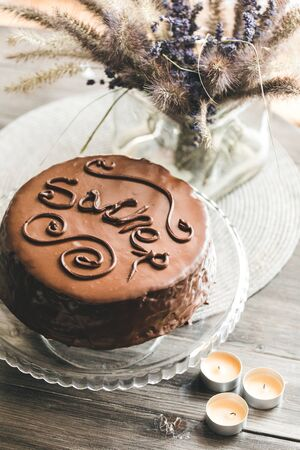 Sacher chocolate cake with an inscription on a glass stand