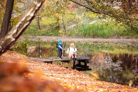 Happy young mother and her son spending time in the autumn park near the pond.