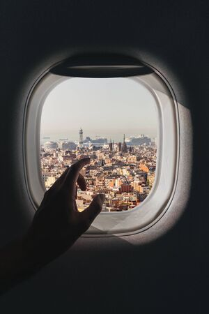 The male hand points a finger towards the aerial panorama of the city of Lisbon in Portugal, which opens from the window of the plane during the flight Banque d'images