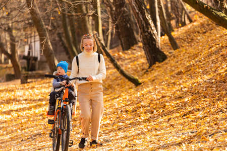 Happy mother leads a bicycle with a child strapped in the back in the autumn park. Reklamní fotografie