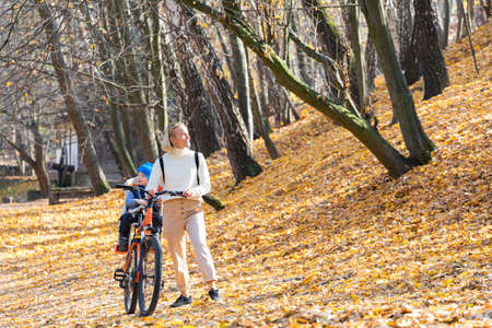 Happy mother leads a bicycle with a child strapped in the back in the autumn park. Banco de Imagens - 156935863