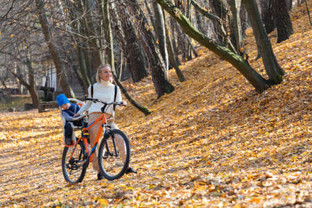 Happy mother leads a bicycle with a child strapped in the back in the autumn park. Banco de Imagens