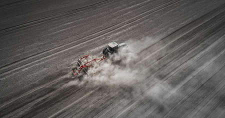 Farmers cultivating. Tractor makes vertical tillage. Aerial view Banco de Imagens