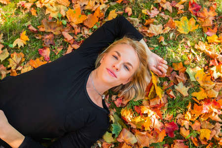 A young woman lies on fallen orange leaves and holds yellow maple leaves in her hand.