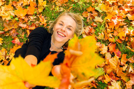 Woman lying on the grass with fallen orange leaves Banco de Imagens
