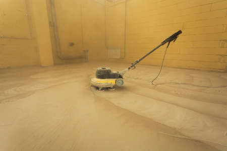 Concrete floor grinding. Construction process. Sanding a concrete floor with a sander in a warehouse
