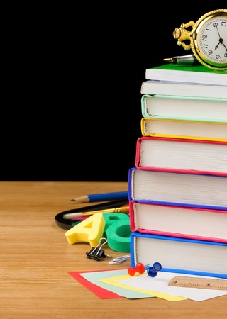 pile of books and school supplies isolated on black background texture photo