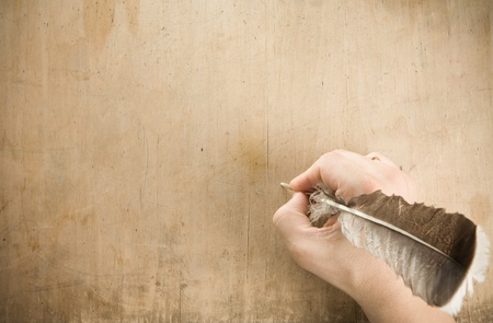 pen and paper: writing hand with pen feather at old wood background texture