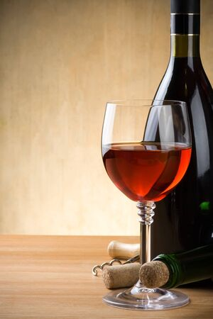 glass and bottle of wine on wood background photo