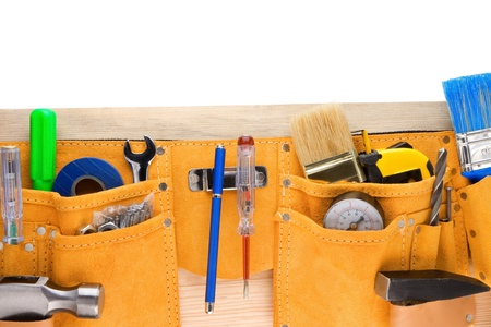 leathern: tools and instruments in leathern belt isolated on wooden texture