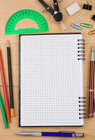 school accessories and checked notebook on wooden texture photo