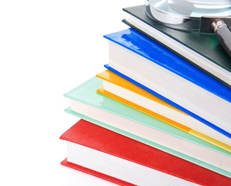 pile of new books and magnifying glass isolated on white background photo