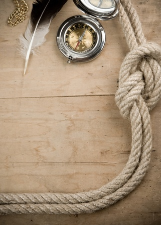 ship ropes and compass on wood background photo