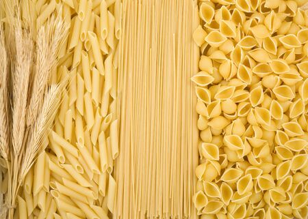 raw pasta and ear of wheat as background photo