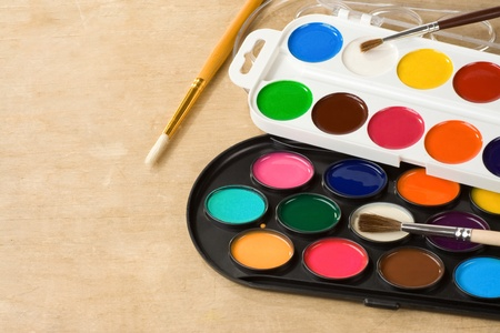 paint brush and painters palette on wooden background photo