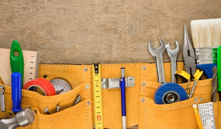 leathern: tools in leathern belt on wooden texture Stock Photo