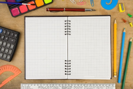 school accessories and checked notebook on wooden table photo