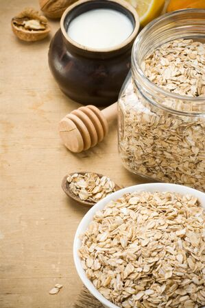 eat right: cereals oat flake and healthy food in plate on wood background