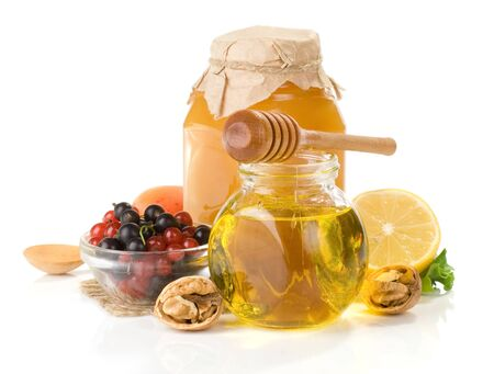 glass jar full of honey, lemon and berry isolated on white background photo