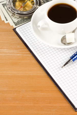 notebook and coffee with dollar on wood table photo