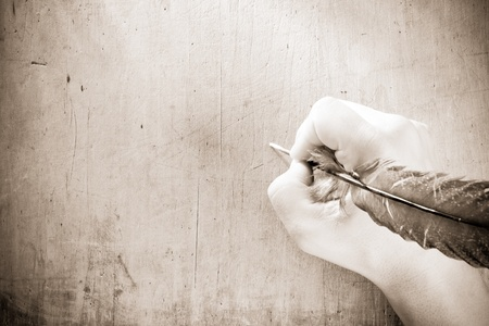 writing hand with pen feather on sepia photo