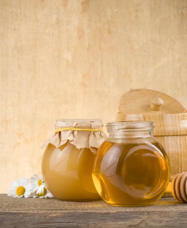 glass jar full of honey and stick on wood background photo