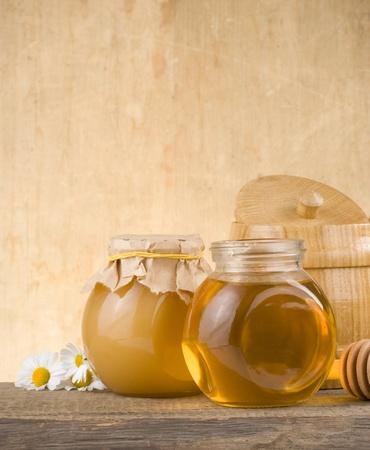honey pot: glass jar full of honey and stick on wood background