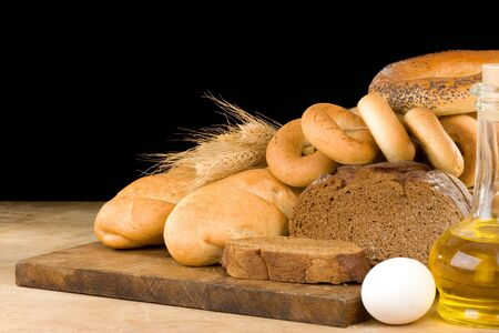 bread and bakery products on wood isolated at black background photo