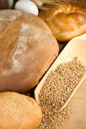 bakery products and wheat grain on wooden texture photo