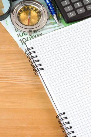 notebook and euro with compass on wood table photo