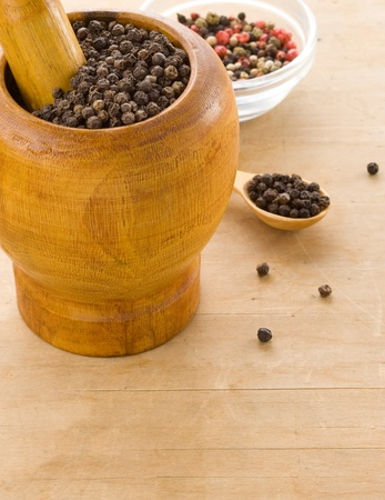 pepper spices and mortar with pestle on wooden texture photo