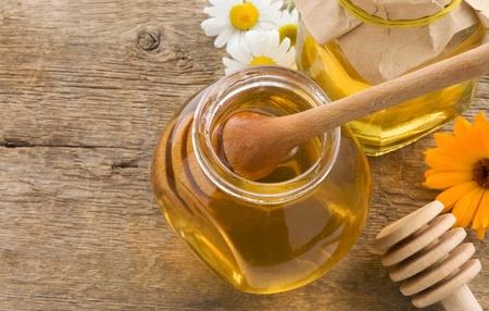 jar of honey and flowers on wood background photo