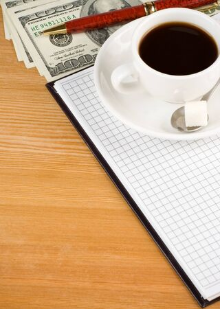 cup of coffee and notebook with dollar on wood table photo