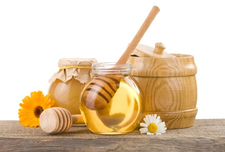 jar of honey and stick isolated on white background photo