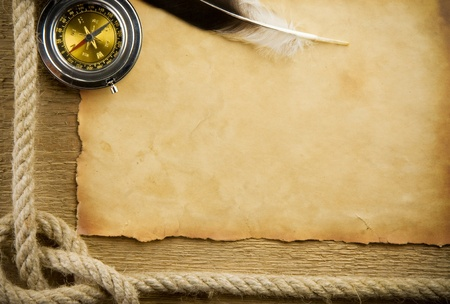 parchment paper and feather with rope on wood photo