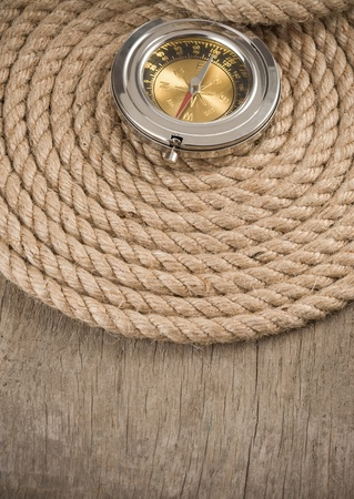 lashing: ship ropes and compass on wooden background Stock Photo