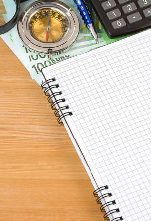 notebook and euro note on wood table photo