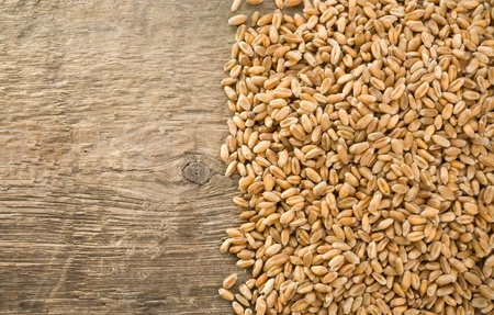 wheat grain on wood texture background photo