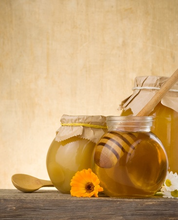 jar of honey and stick on wood background photo