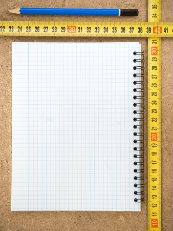 notebook and tape measure on wood texture
