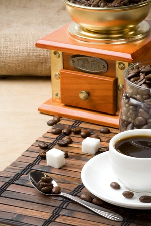 cup of coffee and grinder with roasted beans photo