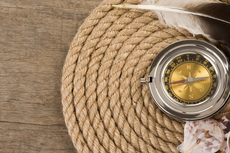 ship ropes and compass on wooden background photo