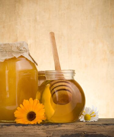 glass jar of honey and stick on wood background photo