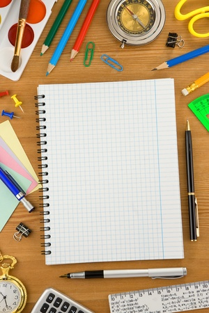 school accessories and checked notebook on wood texture Stock Photo