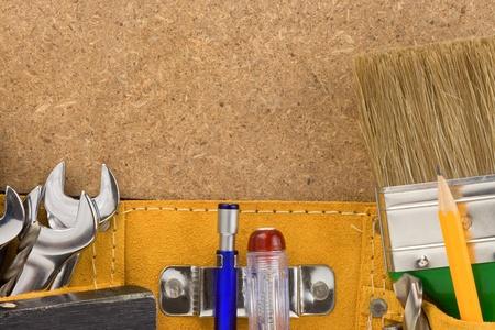 suede belt: tools in belt on wooden texture