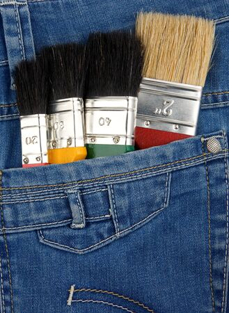 set of paintbrushes on jeans texture photo