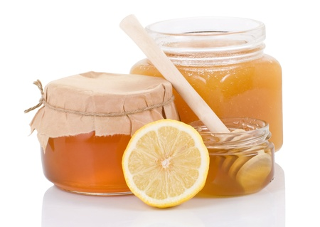 a jar stand: glass pot full of honey and lemon isolated on white background Stock Photo