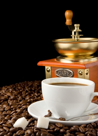 cup of coffee and gold grinder on beans photo